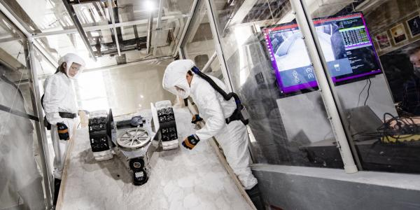 Student researchers watch a lunar rover running slope tests in a fully enclosed chamber       that recreates the moon's dusty conditions. They took first place in the 2020 Breakthrough,       Innovative and Game-changing (BIG) Idea Challenge run by the National Aeronautics       and Space Administration (NASA).