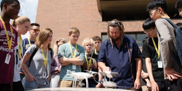 James Bialas does an aerial drone demonstration for students attending the Surveying       Summer Youth Program exploration at Michigan Technological University. Drones are       one tool in the remote sensing arsenal. Image Credit: Peter Zhu