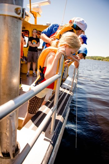 Students watch a Secchi disk dropped over the side of the R/V Agassiz to measure the water clarity.