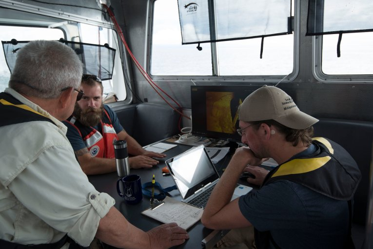 Guy Meadows (left) and Chris Pinnow (right) of Michigan Technological University discuss sonar imagery with Thunder Bay National Marine Sanctuary Archaeologist John Bright (center).