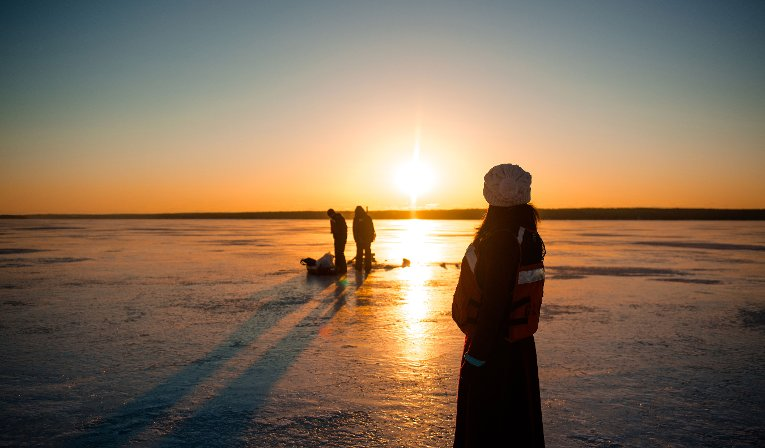 Scientists from the Great Lakes Research Center drill into the ice to drop waterproof nodes into the water to detect acoustic signals.