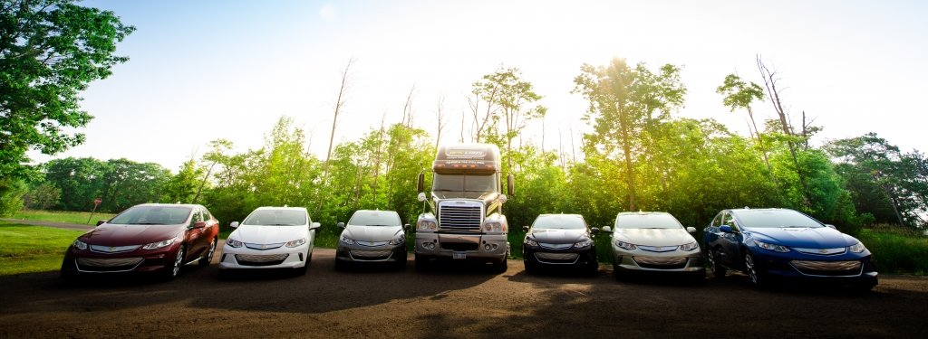 cars in a semicircle with a semi-truck in the middle and trees in the background