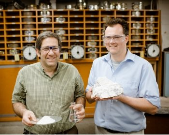 Two men stand next to each other holding gypsum and plaster of Paris.