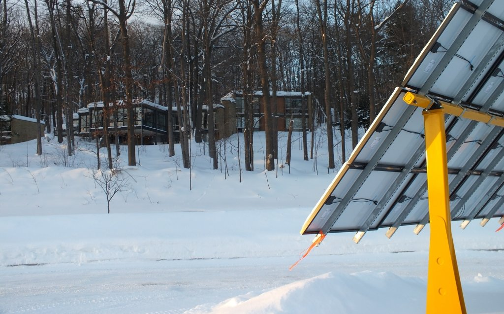 Sunlight shines on solar panels mounted outdoors in the snow in a parking lot near trees