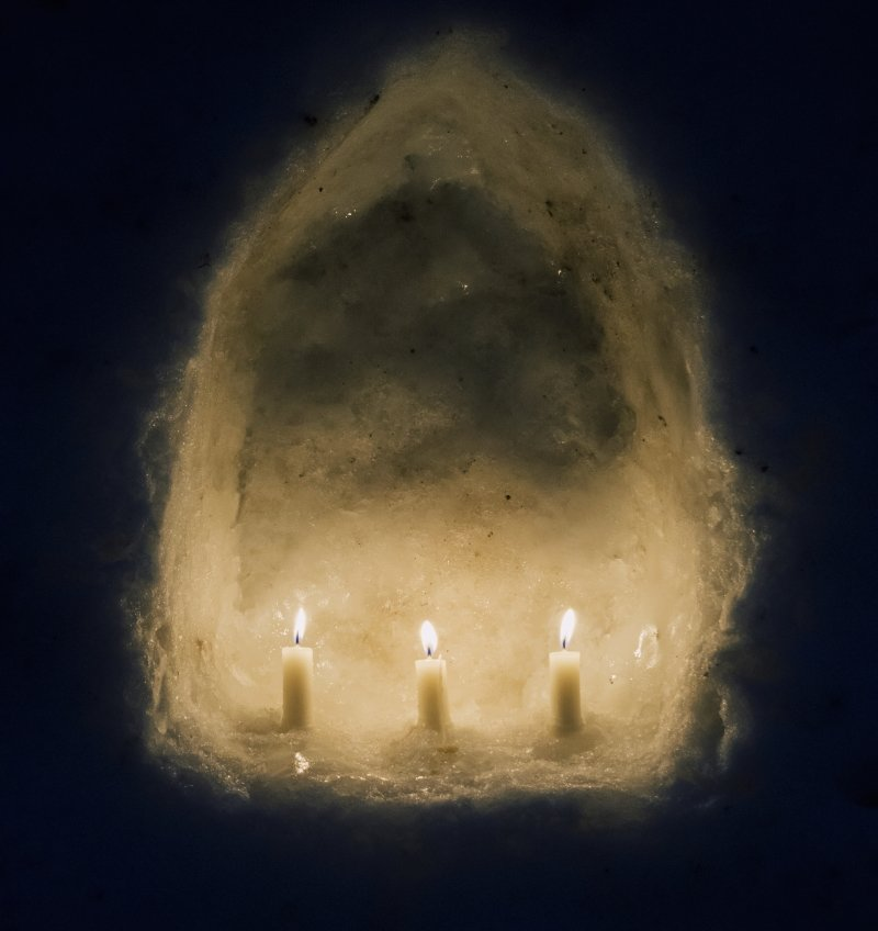 candles in an arch made of snow
