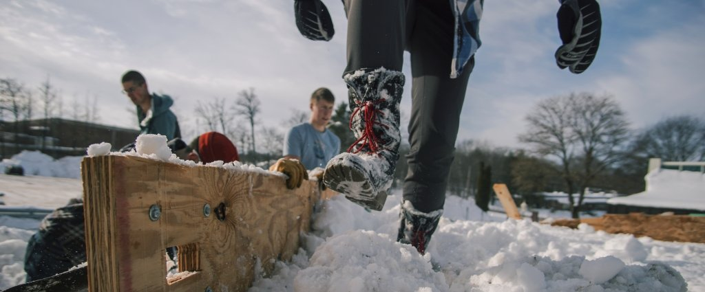 a boot pushing down snow in a wooden form and two students packing snow