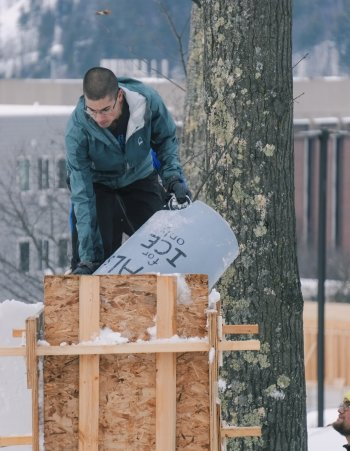 A male student holding a blue bucket standing on top of snow in a wooden form