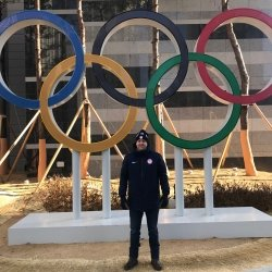 Man standing in front of Olympic rings.
