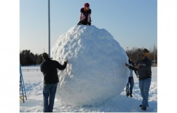 a young woman on top of a giant snowball and other students standing around the giant snowball outdoors in the snow