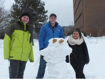 Two young men and one young female college student stand behind a snowman with dried flower eyes with a Husky statue in the background