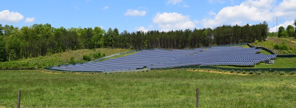An array of solar panels in a field.
