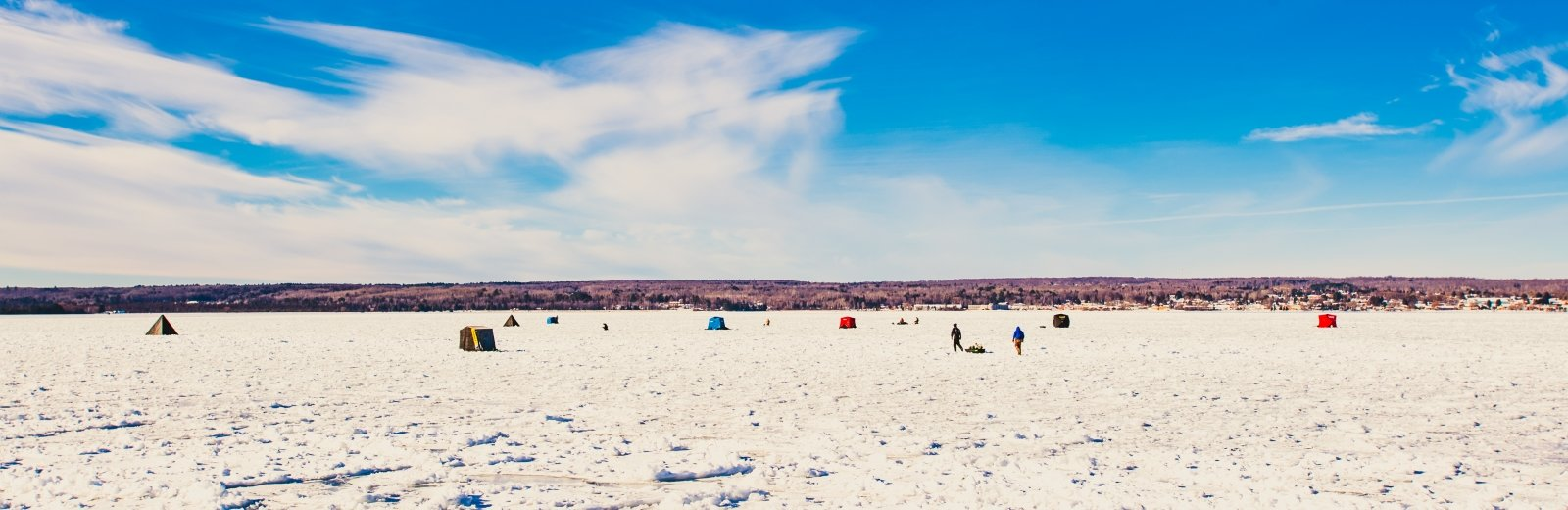 A wide landscape with blue sky and white ice dotted with people and ice fishing huts.