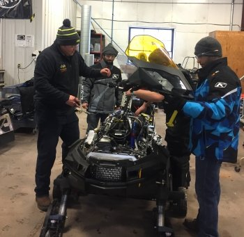 Students gather around a snowmobile to put the outside casing back on it.