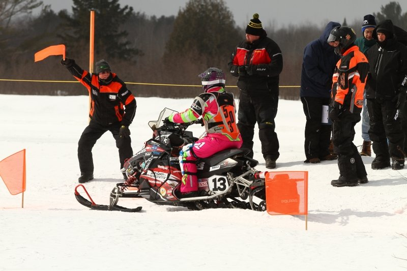 A man raises an orange flag in front of a snowmobile rider waiting to start a race.