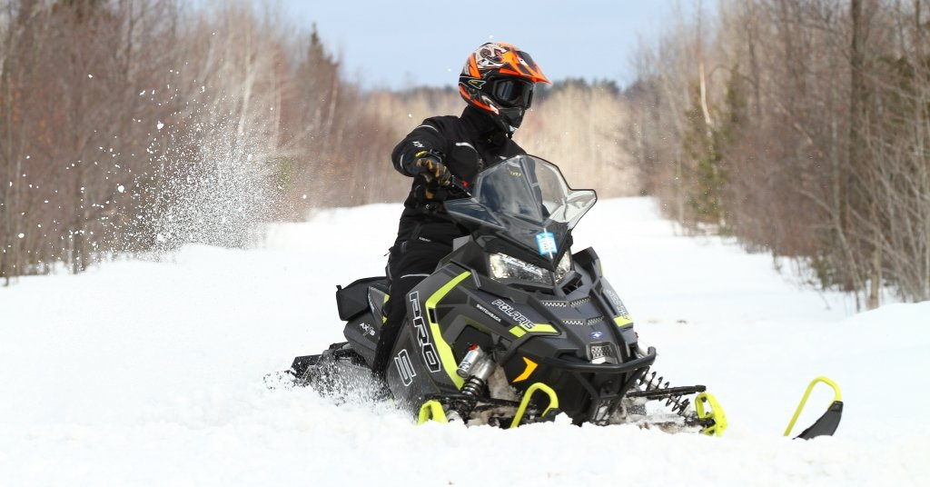 A snowmobile rider wearing an orange helmet rides a black and bright yellow snowmobile.