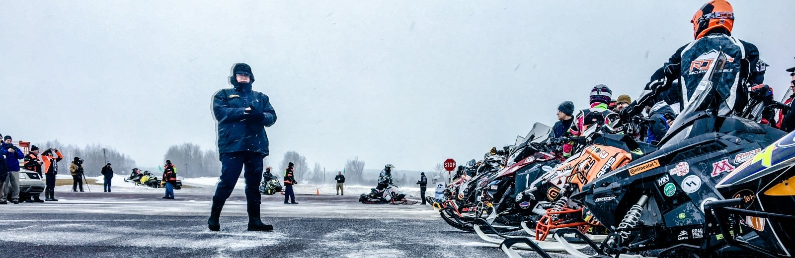 A man standing next to the lineup of snowmobiles and their riders.