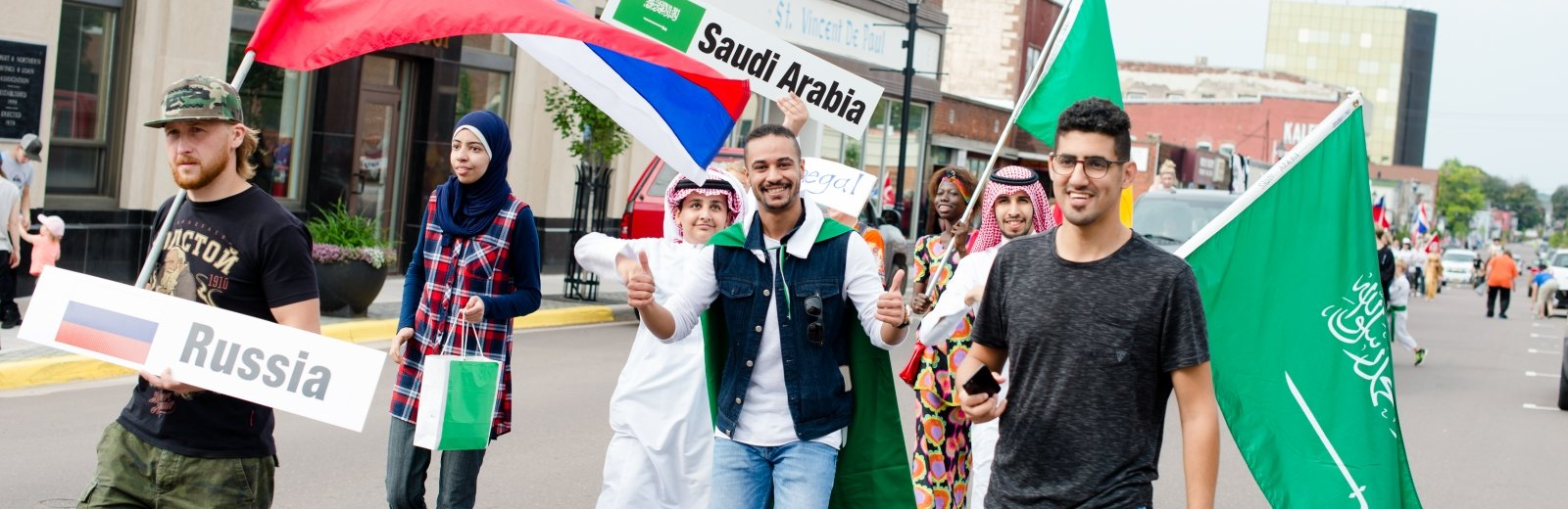 men carrying Saudi Arabia, Senegal, Russia flags and a woman carrying a bag smiling in a parade on a downtown street in a small town