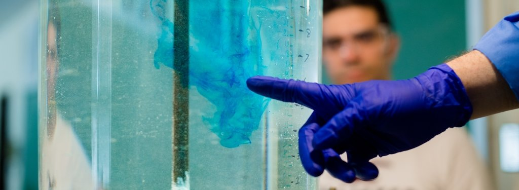 A man's gloved hand points to colorant swirling in a water tank.