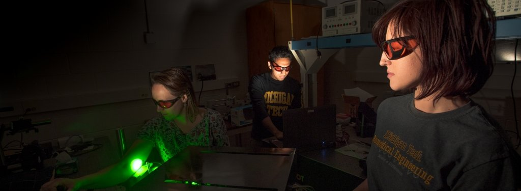 Three people stand around a box-like lab equipment lit only by a green laser