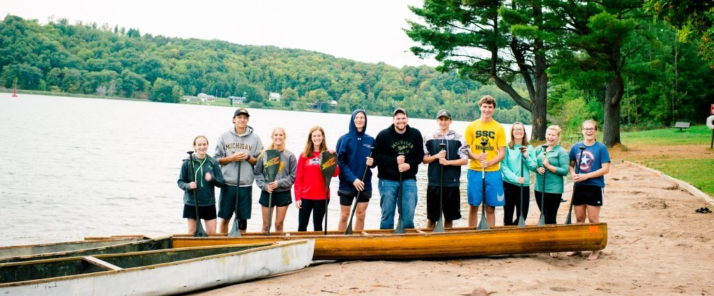 11 young men and women with canoe paddles and two canoes stand on the beach by the water