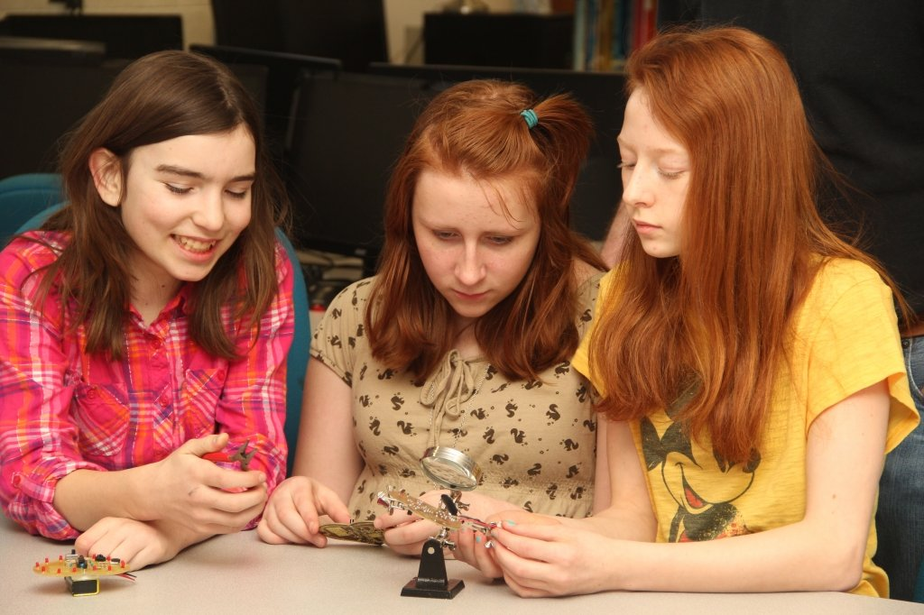 Three young girls look at a circuit board with a hand held microscope.