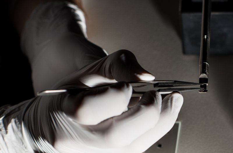 Gloved hands holding fine-tipped tweezers place a rice grain-sized sample holder in place on a pencil-sized instrument