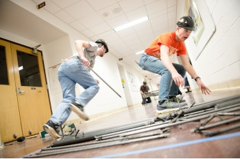 Two young men wearing hard hats run metal pieces to two students building a steel bridge in the hall