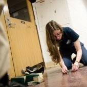 A young woman sets up the screws and bolts on a floor in a hall