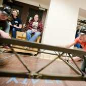 a female and male student wearing hard hats assemble a steel bridge in the hall while two female college students look on