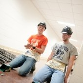 two young men with pieces of steel in a hall wearing hard hats and carpenters belts smiling