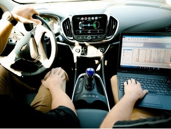 Within the cab of a car, two people sit. One holds the steering wheel and the other runs a laptop.