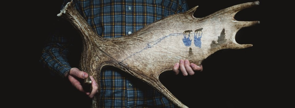 A man in blue flannel holds a moose antler.
