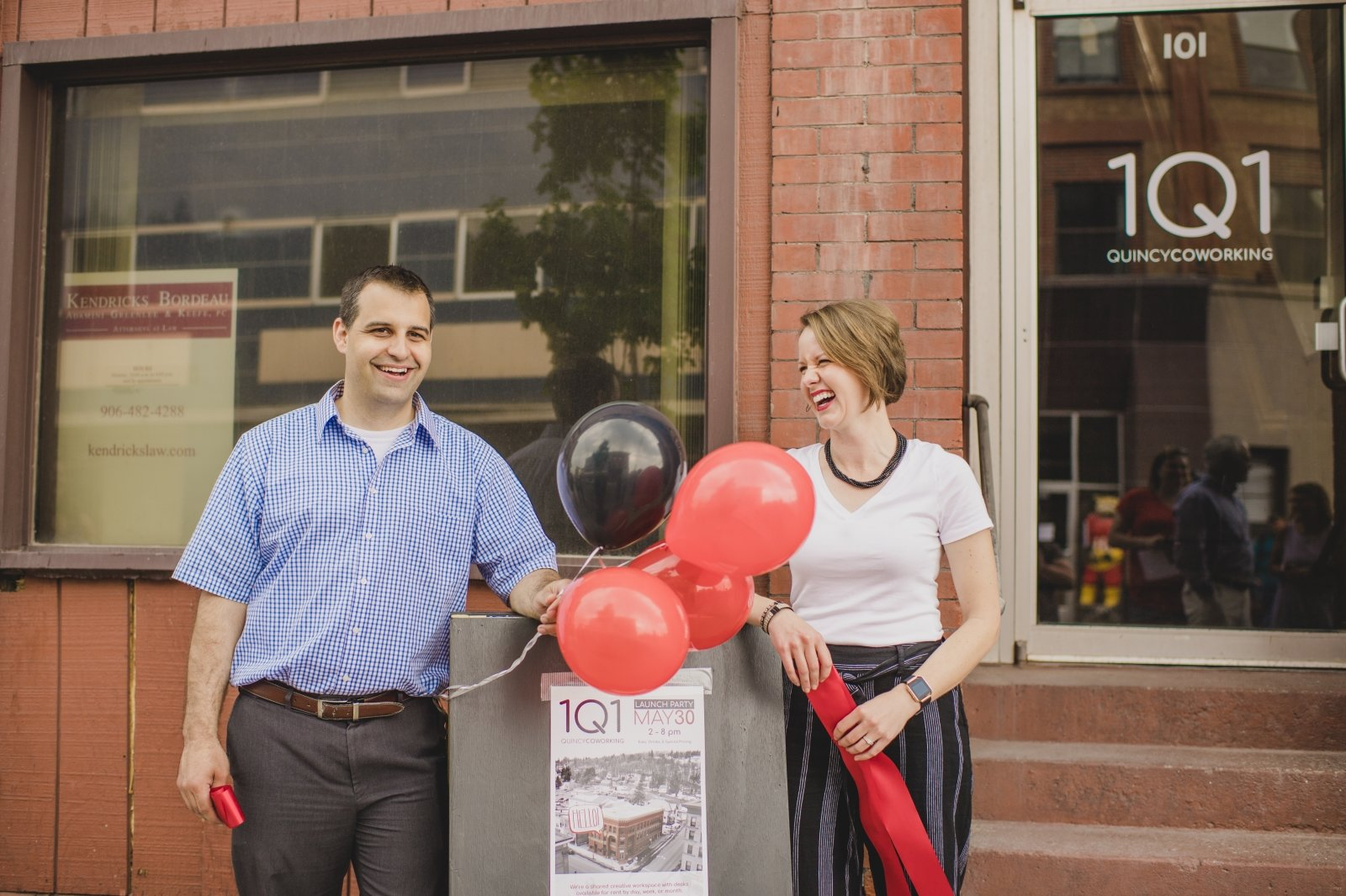 A man and a woman smile while standing next to a sign that reads 1Q1 launch party. There are balloons and each hold a ribbon.