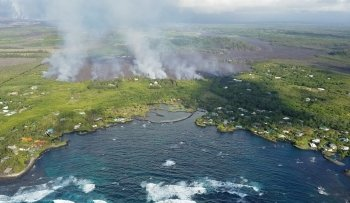 Kapoho Bay in Hawaii with smoke rising from lava.