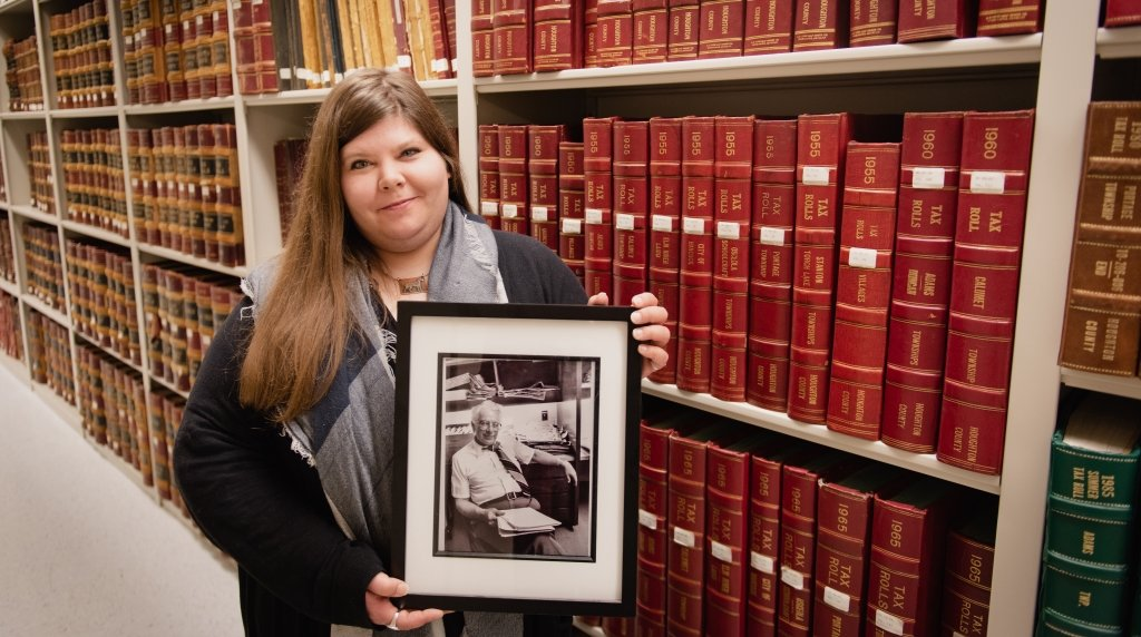 A woman with long hair holds a black and white framed photo of an older man with stacks of bound library volumes in the background