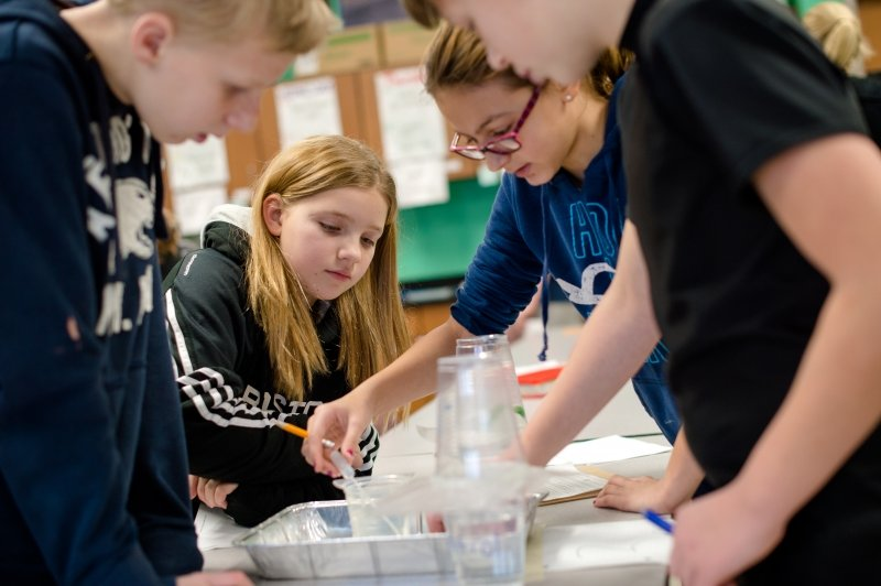 four children work on a plastic tube and water experiment in a classroom with green walls