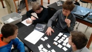 four young boys at black table with white pieces of paper on it and a see-through plastic container holding pencils in a science classroom looking at a science and engineering problem to solve