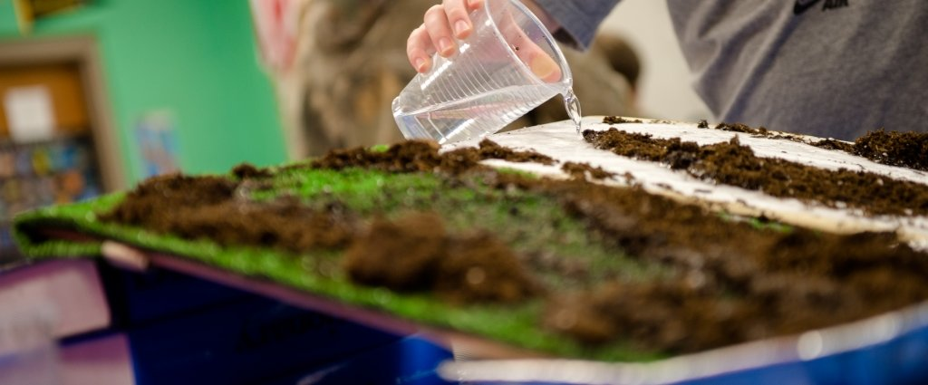 cup of water in a person's hand being poured over a pan of soil and green material with a green background in a science experiment in a classroom