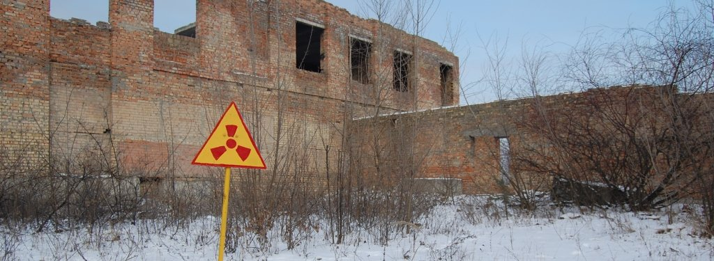 Nuclear radiation sign in front of damaged building.