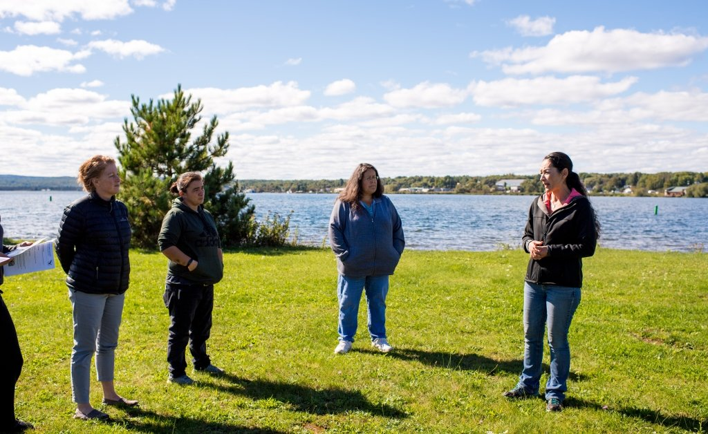 Four people stand in a semi-circle on grass in front of Lake Superior