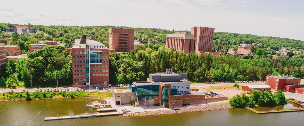 Aerial view of Michigan Technological University Campus with trees and brick skyscrapers in the background and a dock with boats