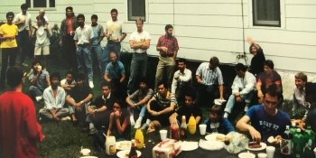 a group of young men and women by a picnic table sitting and standing on the grass with a white sided house in the background eating food together at an international cookout