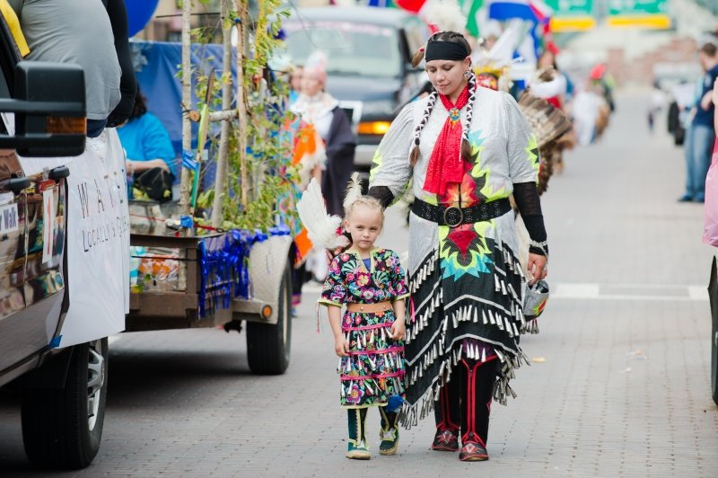A mother and her little daughter walk in native american regalia walk next to a float with branches on it on a downtown street outside in a parade