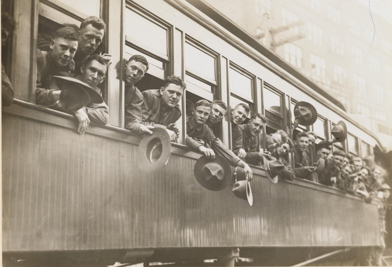 World War I soldiers black and white photo with their heads out the windows of a train in Cincinatti, Ohio waving to the unseen crowd at the train station
