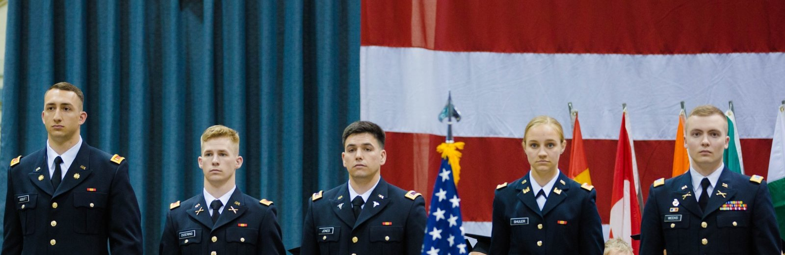 Four Army ROTC cadets and one Air Force ROTC cadet stand at attention on stage at commencement. American flag in background and foreground. Headed caps of graduates in audience in foreground too.