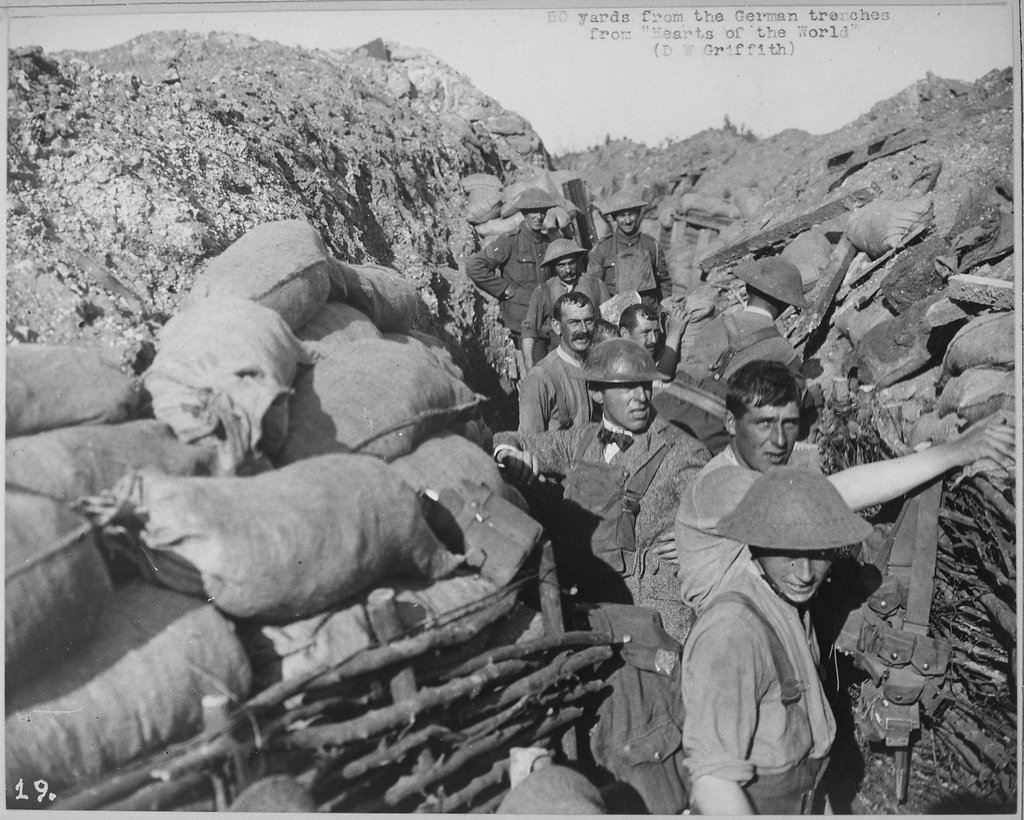 soldiers and filmmaker DW griffith in an earthen and sandbagged trench new the german lines after a bombing in a black and white World War I photo from the national archives the men are wearing metal helmets