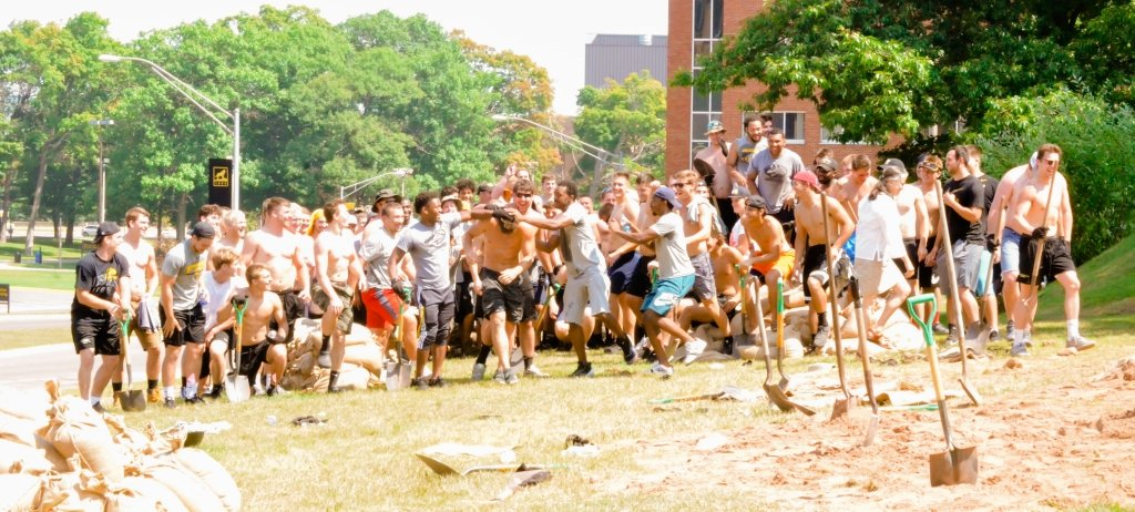 100 male football players in shorts and an older female professor gesture excitedly on a grassy hill in front of shovels, sand and a sandbag with college campus brick buildings and large green and leafy trees in the background