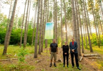 Two men and a woman stand beneath a cloth banner in a pine tree grove.