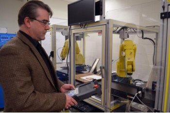 A man stands next to a yellow robotic arm in a lab
