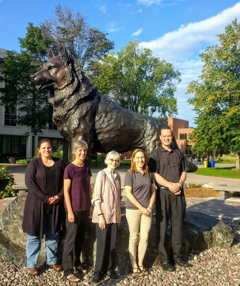 group of people standing in front of the husky statue